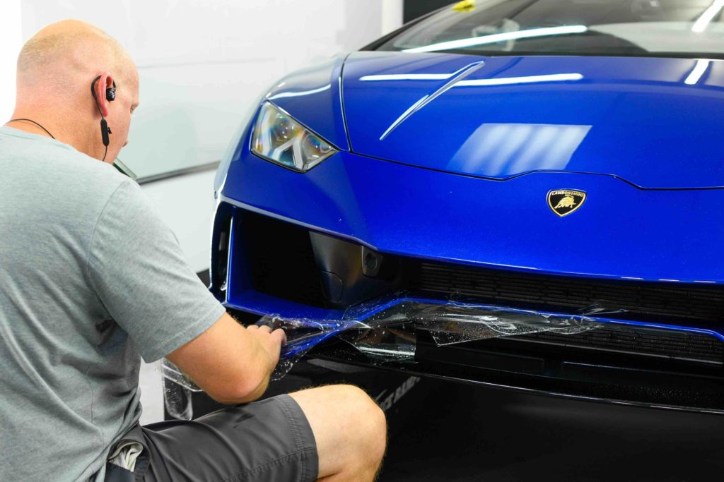paint protection film being applied to a blue car