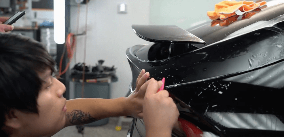 A Sun Stoppers worker applying paint protection to a Tesla